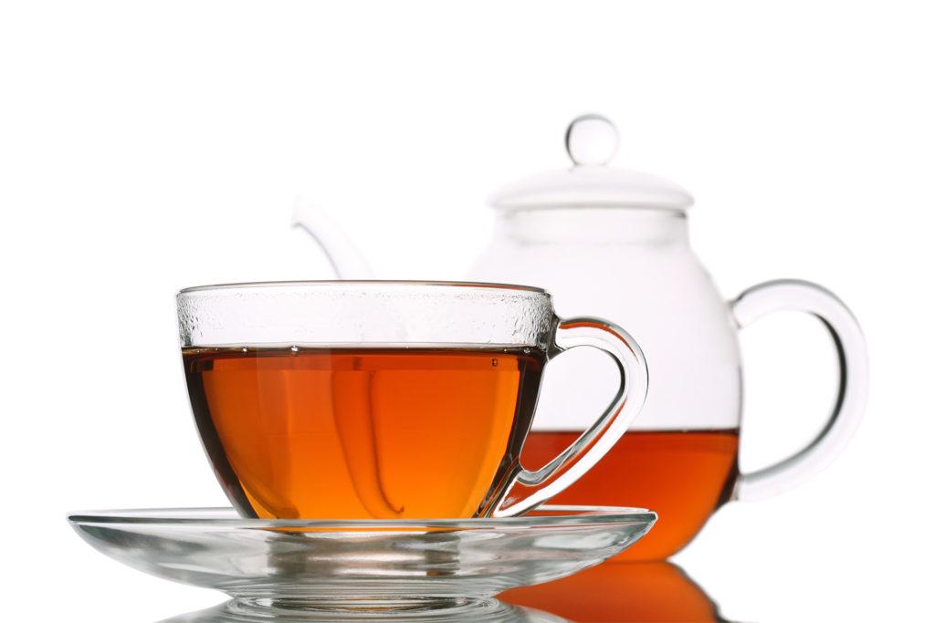 Glass cup of tea beside glass tea pot