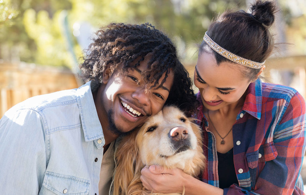 Young couple spend time playing with their cute dog Pic: Istockphoto