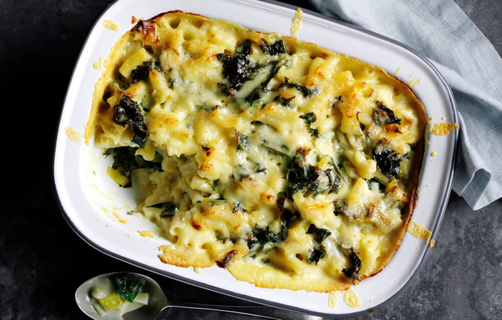 Oval dish of baked macaroni cheese with kale