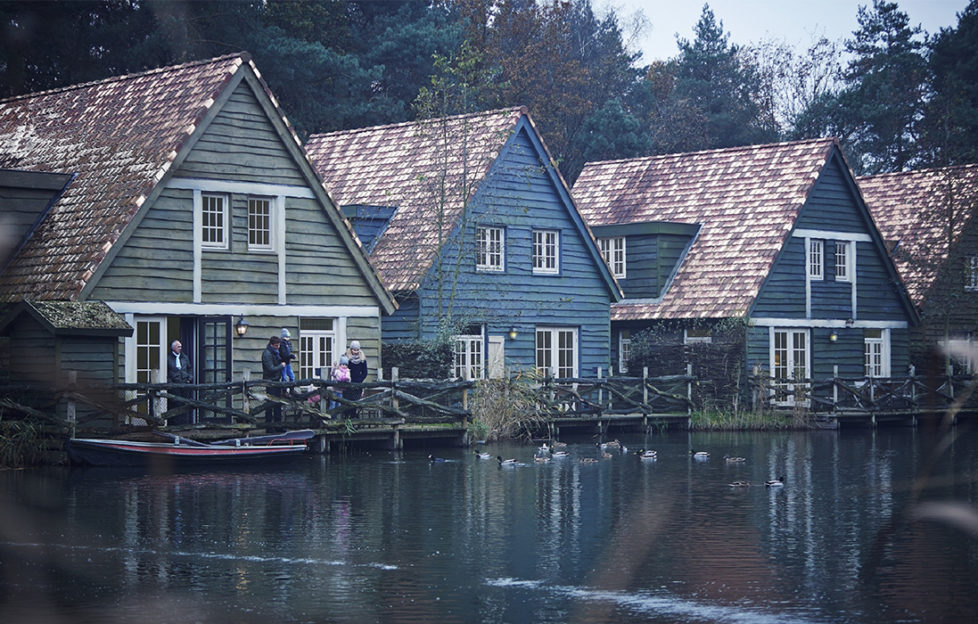 Three Scandinavian wooden houses, stained in green and blue with wide reddish tiled roofs, set beside a lake, family with children on the veranda wearing warm clothes