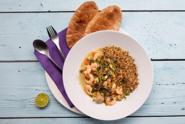 Bowl of green Thai prawn curry with brown rice, toasted mini naan bread and half a lime