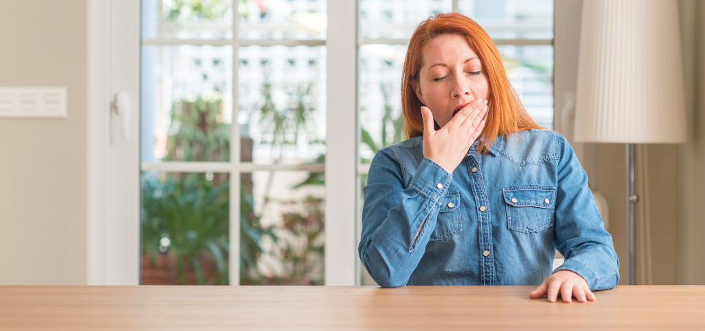 Redhead woman at home bored yawning tired covering mouth with hand. Restless and sleepiness.