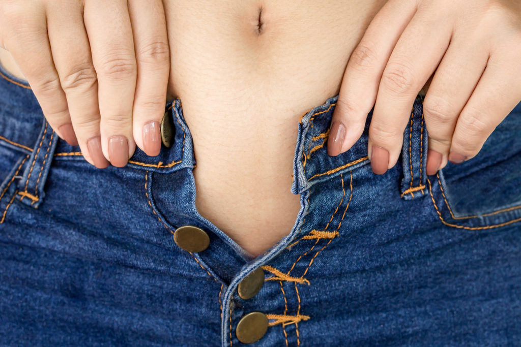 Close up of a woman's hand trying to fasten jeans that are too small