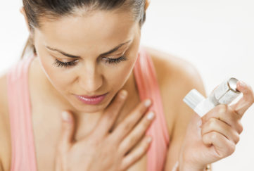 Young woman having asthma attack. She is holding asthma inhaler. Pic: Istockphoto