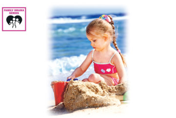 Little girl sitting with bucket and sandcastle, sea behind, long blonde plait and red bikini