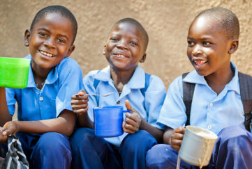 Three schoolboys in Zambia enjoying food provided by Mary's Meals Pic: Chris Watt