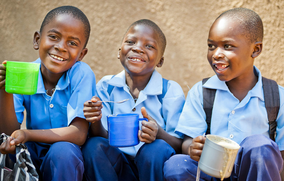 Three schoolboys in Zambia enjoying food provided by Mary's Meals Pic: Chris Watt