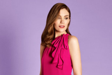 head and shoulders of brunette in cerise high necked sleeveless dress, with a soft pleated ruffle hanging drom left shoulder