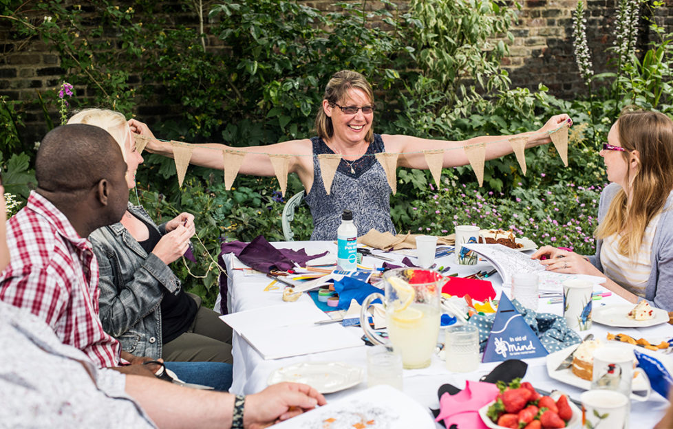 People sitting around a table covered in craft materials at a Crafternoon event. One woman is proudly holding up a string of home made bunting.