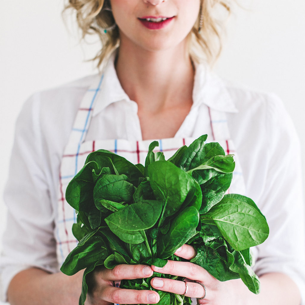 Young woman holding a bunch of fresh spinach stems in both hands against her stomach