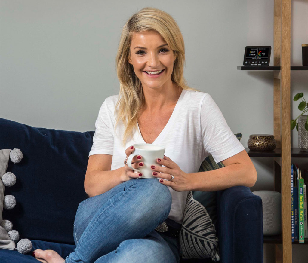 Countryfile presenter Helen Skelton sitting on a black leather sofa with a mug of tea. One of her energy saving tips is not to fill the kettle with more water than you need.