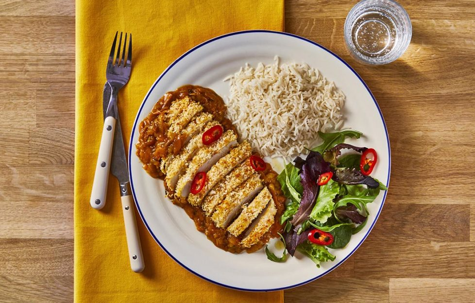 Golden breaded chicken brest, cut in slices, on bed of rich curry sauce with portion of rice and green salad with red chilli