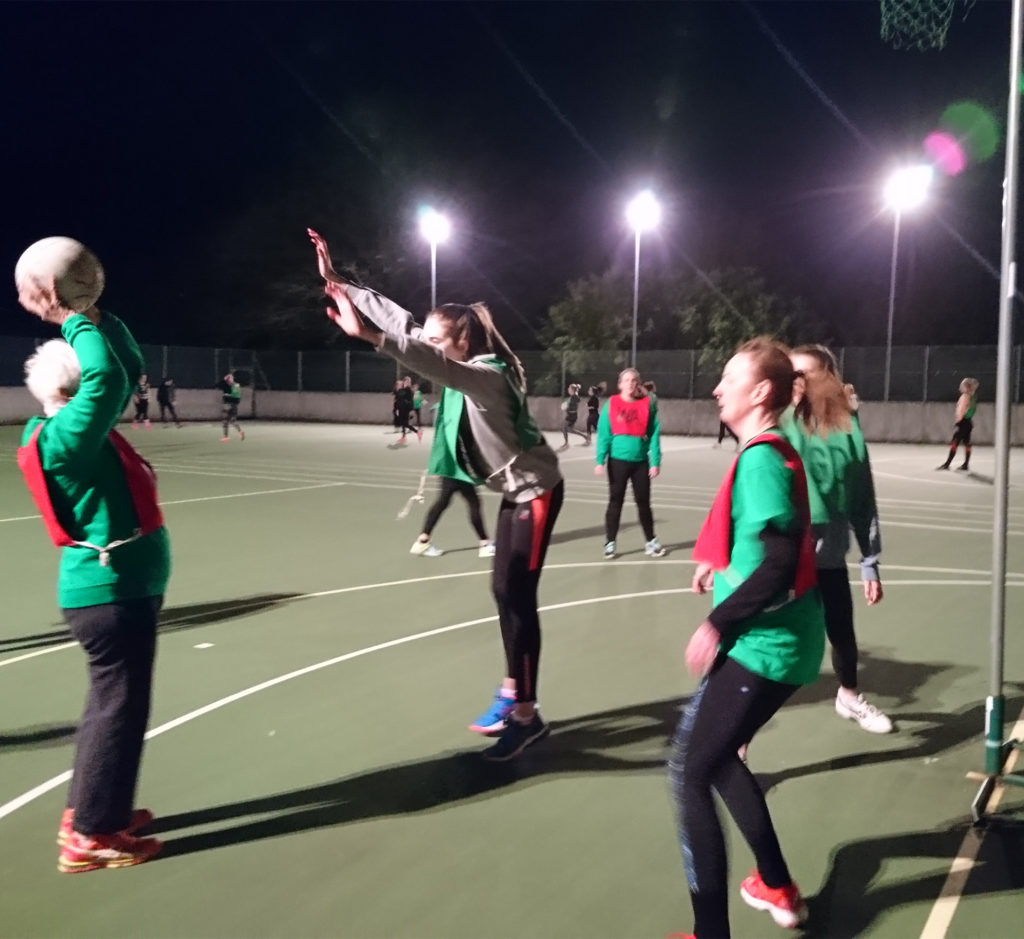 Elderly lady holding netball above her head as she aims to throw it into the basket, other players defending