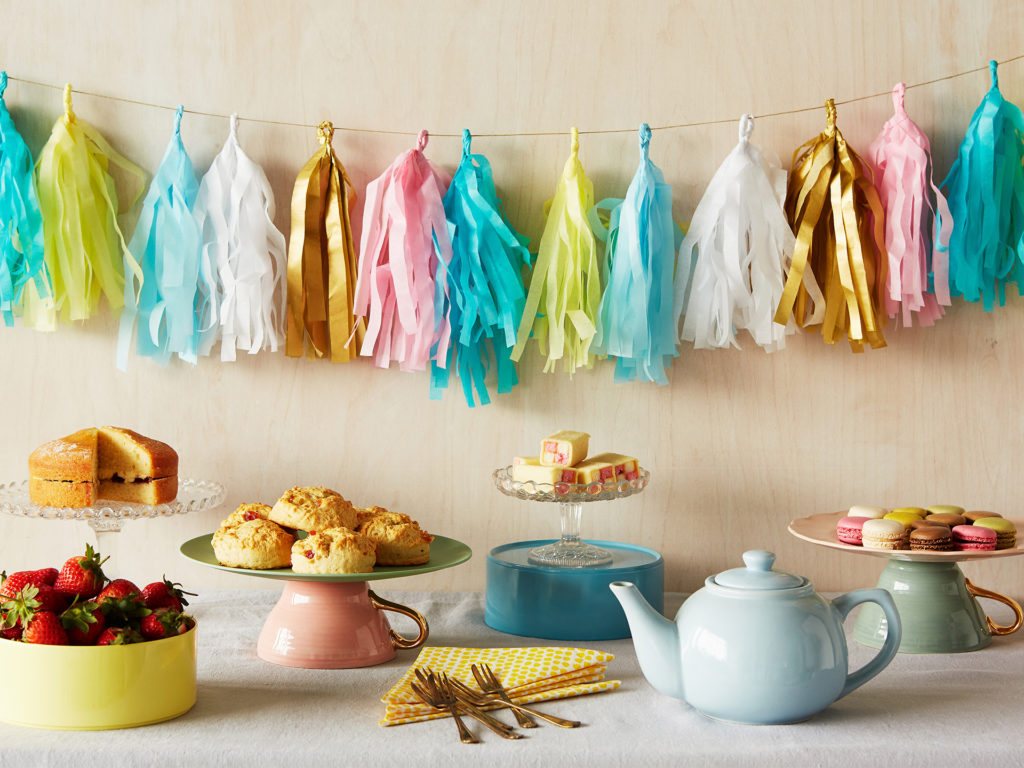 Table with teapot, cups and plates of cakes, string of handmade streamer decorations on wall behind, all ready for a Crafternoon event