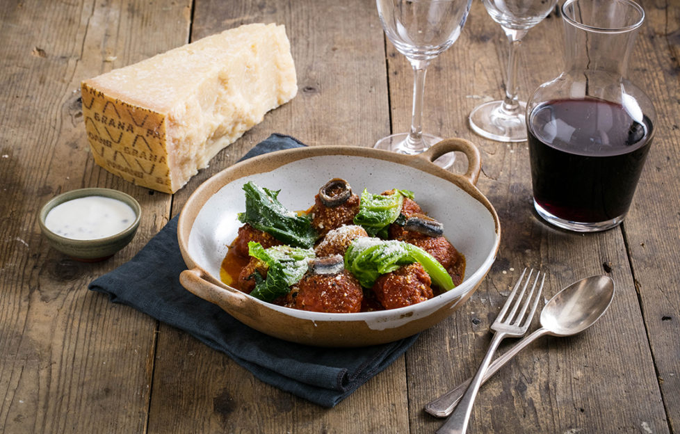 Bowl of four meatballs in tomato sauce, with finely grated grana padano cheese and wilted leaves, and a glass of red wine