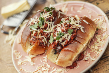 Two long bread rolls with veggie sausages, salsa, grated cheese and garnish