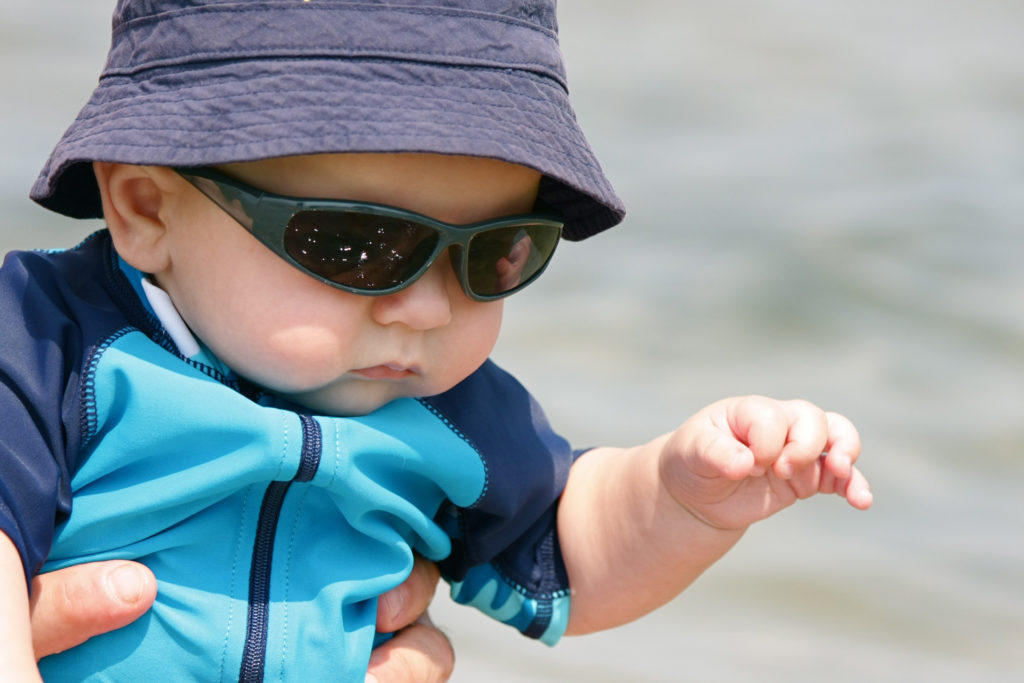 """A baby boy, wearing sunglasses and a sun hat, enjoys a day at the beach."