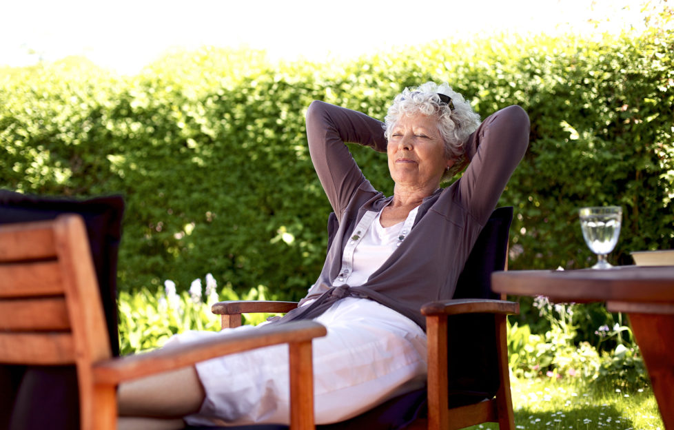 Senior woman sitting on a chair and taking a nap in backyard. Elder woman sleeping in backyard garden