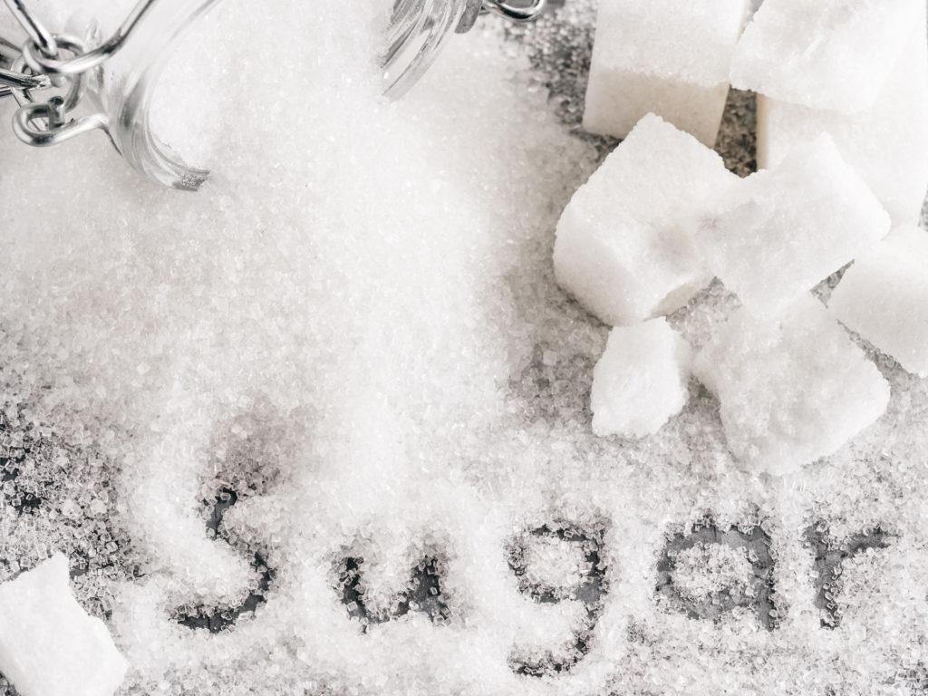 Close up view of word sugar of granulated sugar. sugar cubes. Top view or flat lay.