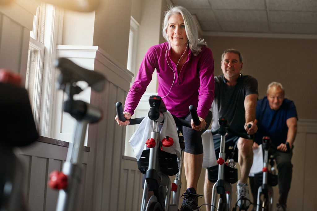 Shot of a group of seniors having a exercising class at the gym - spin class