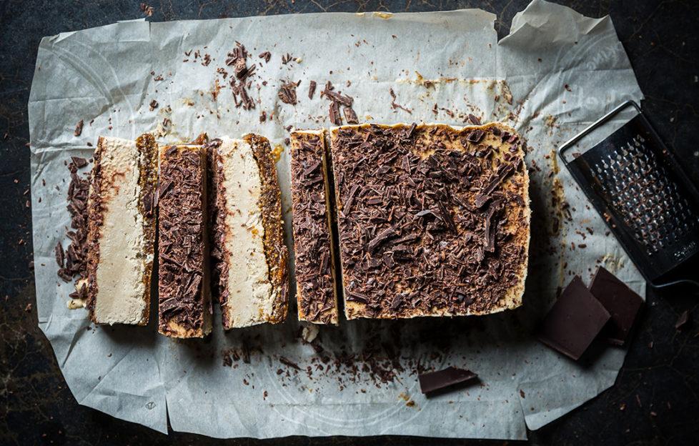 Block of vegan freezer tiramisu dessert, sprinkled with chocolate, four slices cut