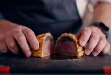 Chef has cur beef wellington in half to show pink meat, dark layer of mushrooms, and golden pastry