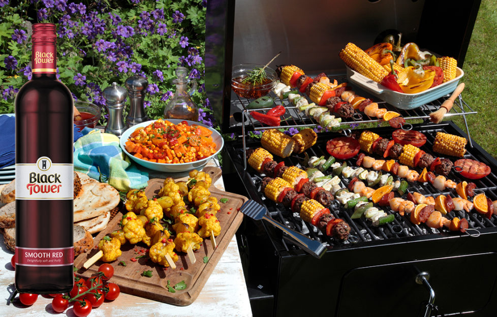 A barbecue grill filled with kebabs with bread and salad at the side and a bottle of Black Tower Smooth Red wine