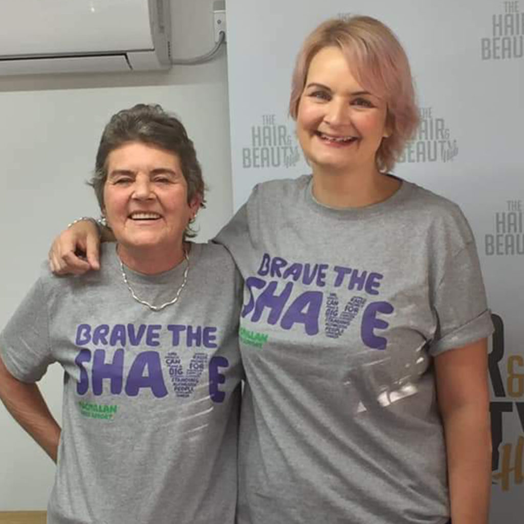 Mother and adult daughter in grey Macmillan t shirts at hairdressers, smiling