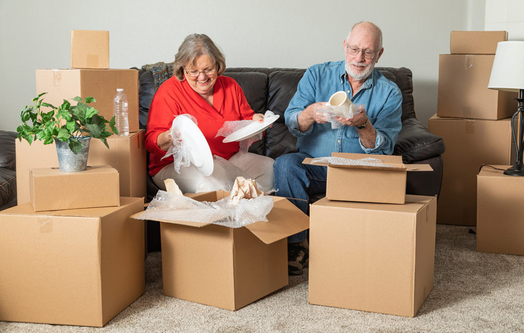 Senior Adult Couple Packing  Moving Boxes.