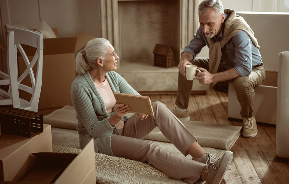 Older wife showing old photo to her husband while taking break from packing cardboard boxes