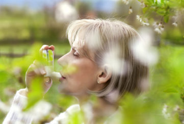 woman in the blossoming garden, using inhaler for asthma
