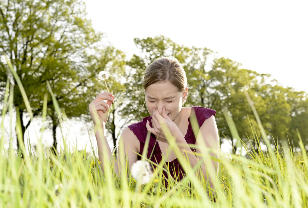Woman with hay fever in field