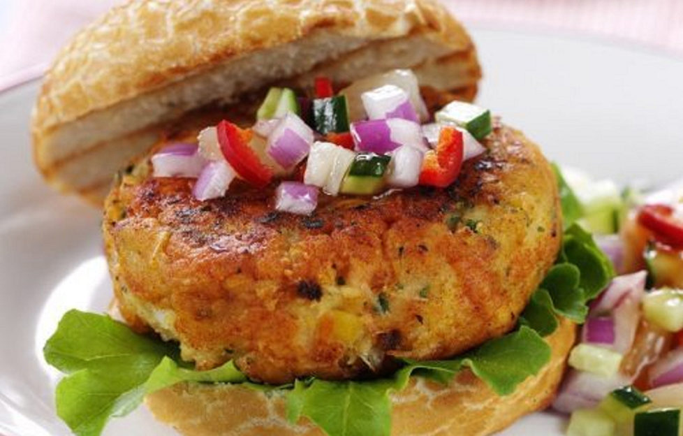 Open crusty white roll with golden brown salmon burger topped with diced red onion, red pepper and cucumbered with