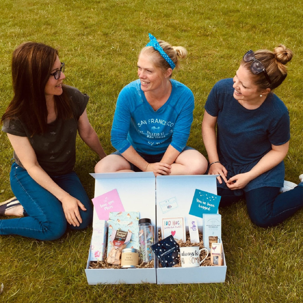 Anna Peters, Lucy Ambler, and Sophie Morris with one of the Box Of Hugs gift boxes