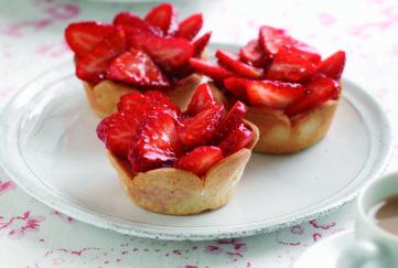 Three glazed strawberry tarts on a plate, cup of tea alongside