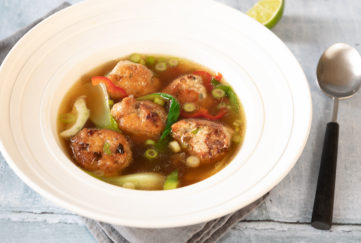 Bowl of 5 chicken meatballs in golden broth with spring onions, chilli and ginger slices