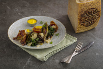 Bowl of salad with cheese, pancetta and big block of Grana Padano on the side