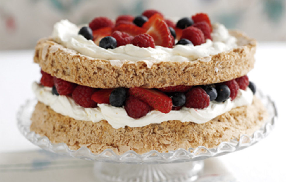 Macaroon cake filled and topped with cream and fresh berries