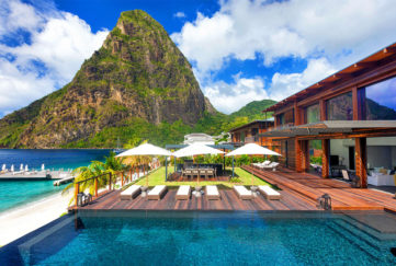 Sugar Beach, A Viceroy resort - steep, wooded mountain behind, holiday home with decking over turquoise water in foreground