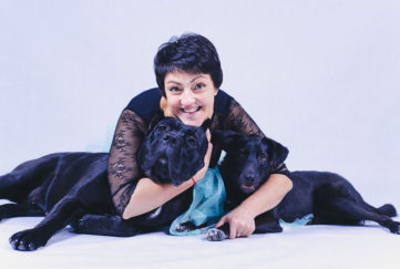 Pets make life happier. Happy mature woman lying on floor hugging two happy black dogs