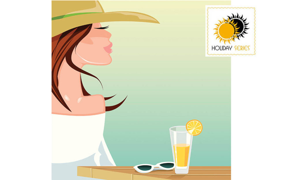 Woman in sunhat, glass of orange juice and sunglesses on cafe table in front of her, looking dreamily into distance
