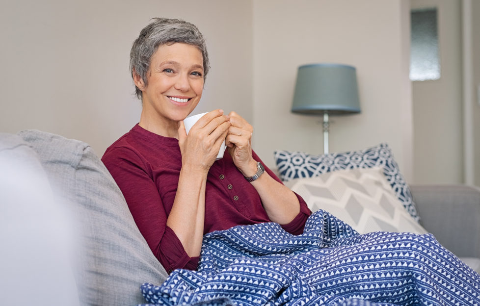 Portrait of smiling senior woman drinking coffee at home while looking at camera. Mature woman sitting on couch with warm blanket wrapped around leg. Happy lady relaxing at home with hot drink.