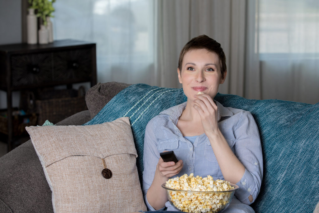Happy mid adult woman eating popcorn while watching a movie at home in living room