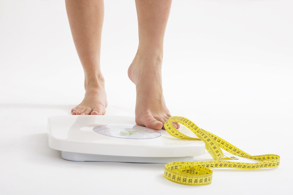 Woman's feet standing on bathroom scales