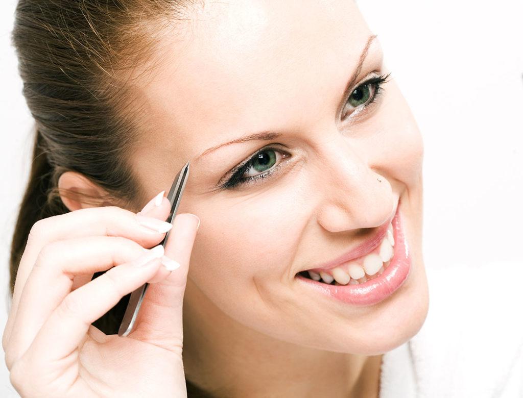 Beautiful woman tweezing eyebrow Pic: Istockphoto
