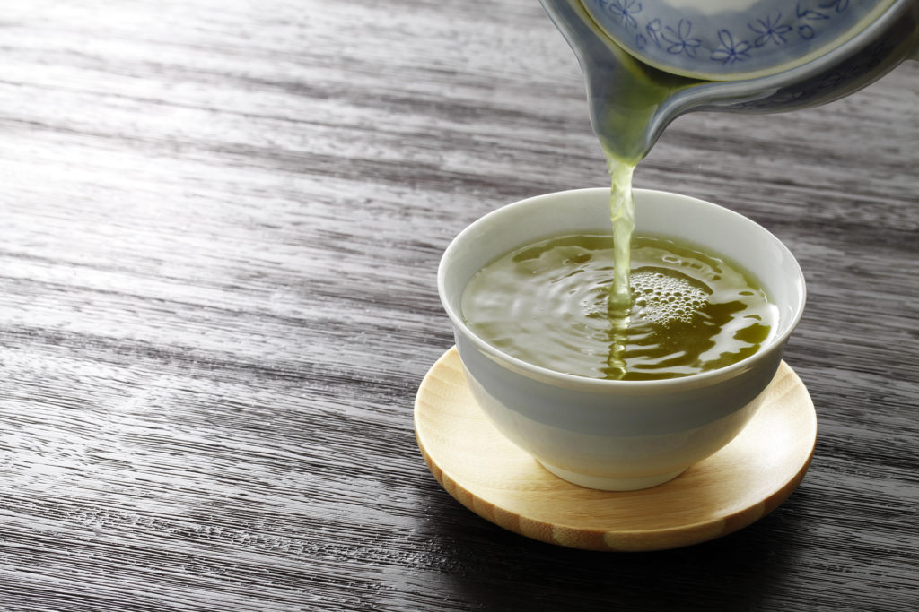 Green tea being poured into a cup