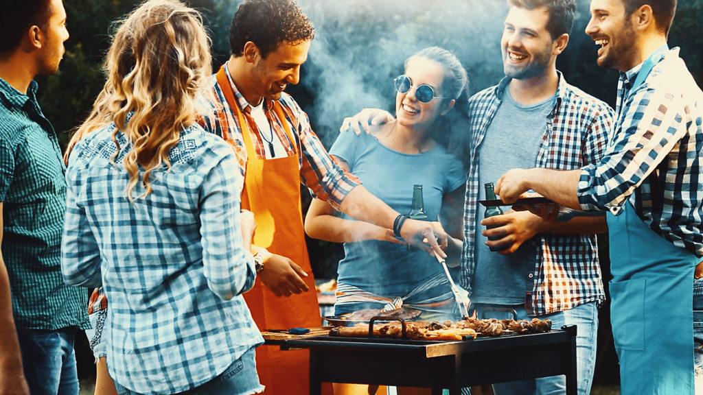 Group of friends around BBQ in garden