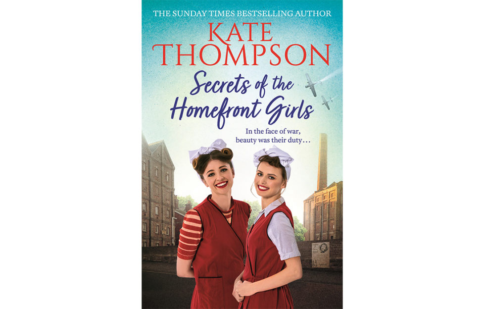 Cover of WW2 novel Secrets Of The Home Front Girls - 2 smiling women in red overalls, white headscarves and red lipstick, factory buildings in background