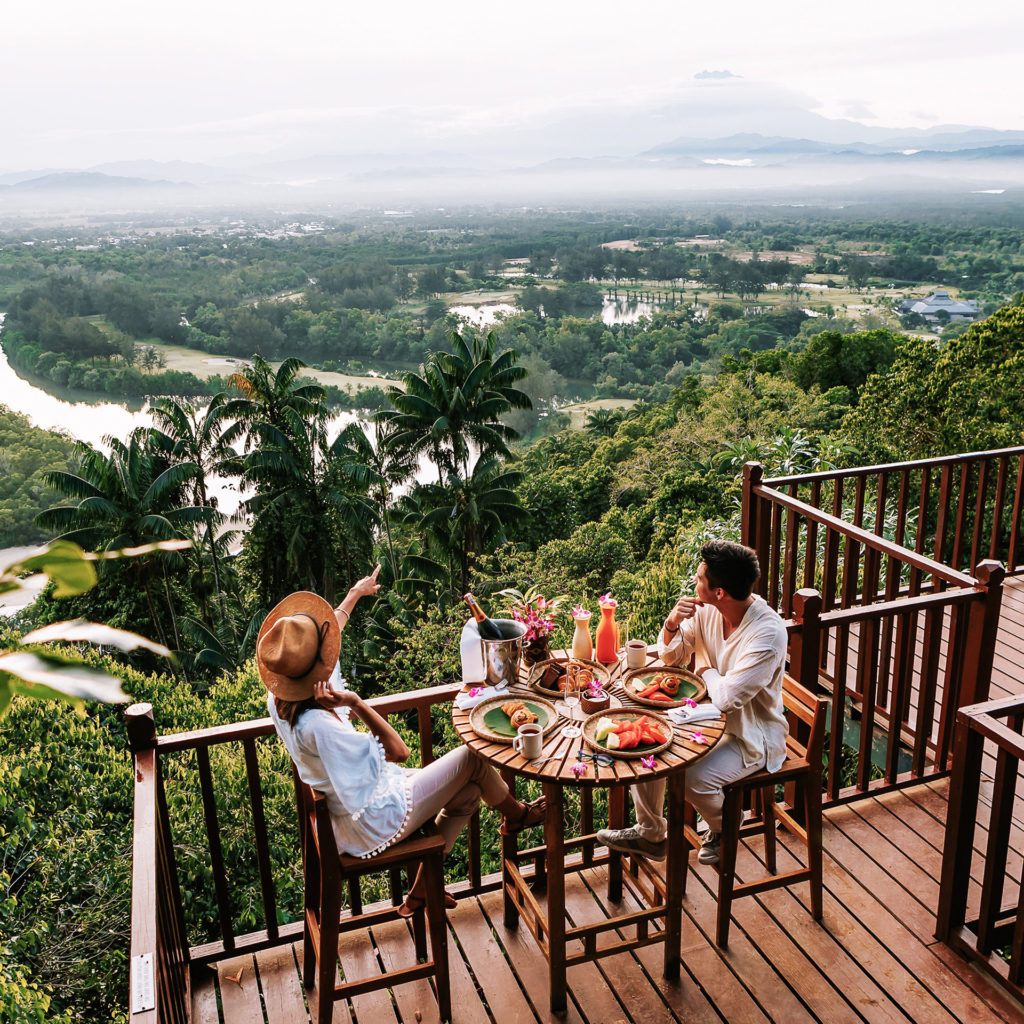 Couple enjoying breakfast on decking looking out over tropical rainforest and river below