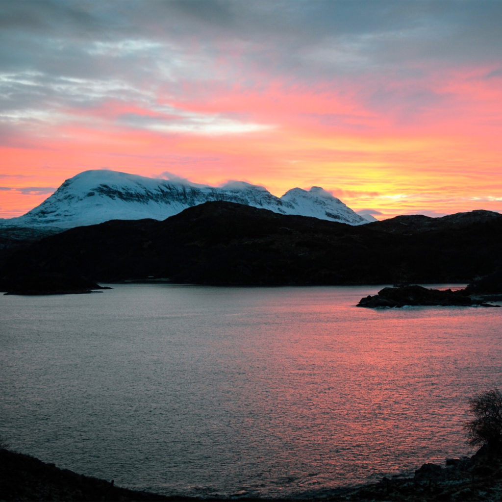 Hills, some snow-covered, at sunset, pink light reflected in sea